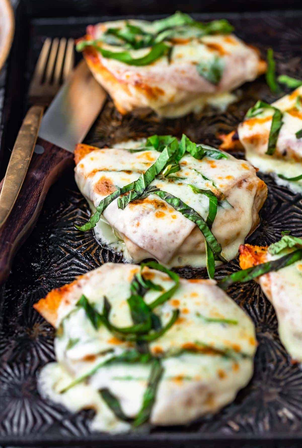 Cheesy Chicken Prosciutto on sheet pan with basil