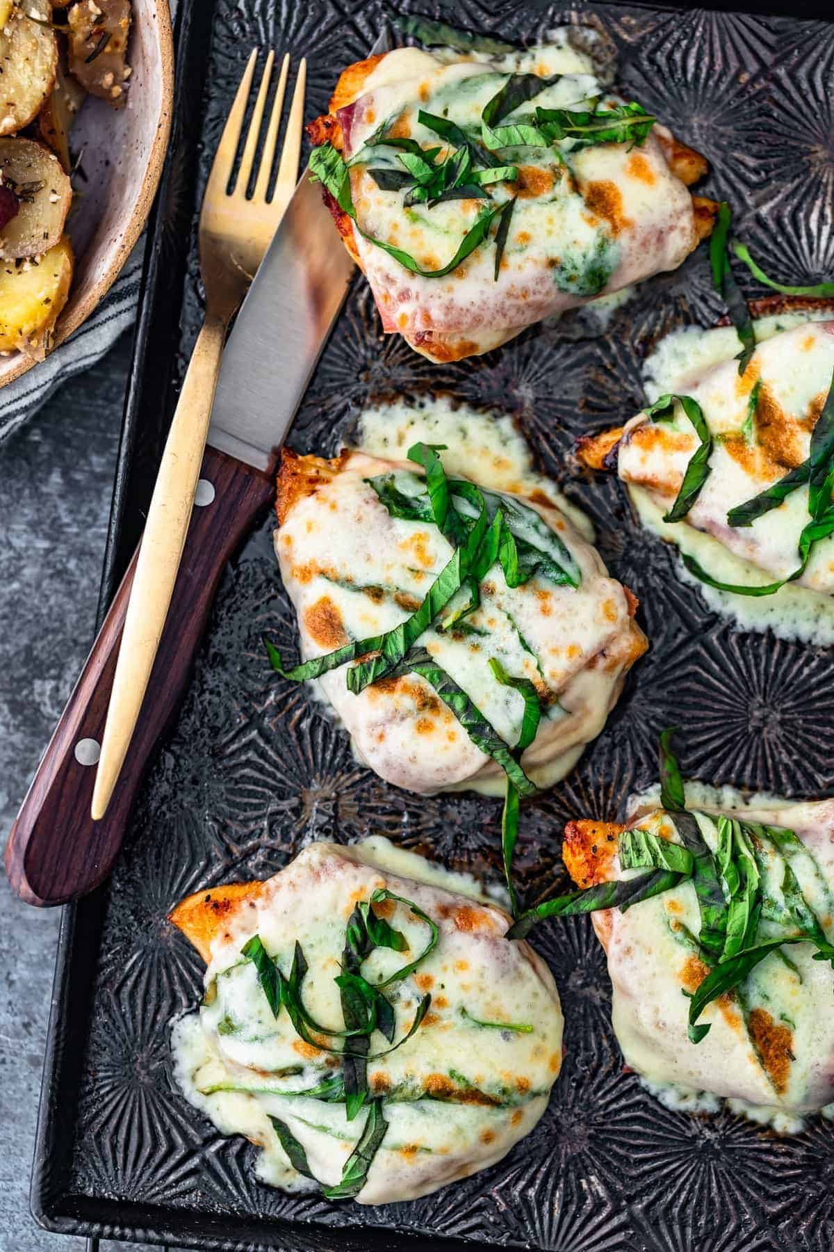 Cheesy Chicken Prosciutto with fresh basil overhead shot on sheet pan