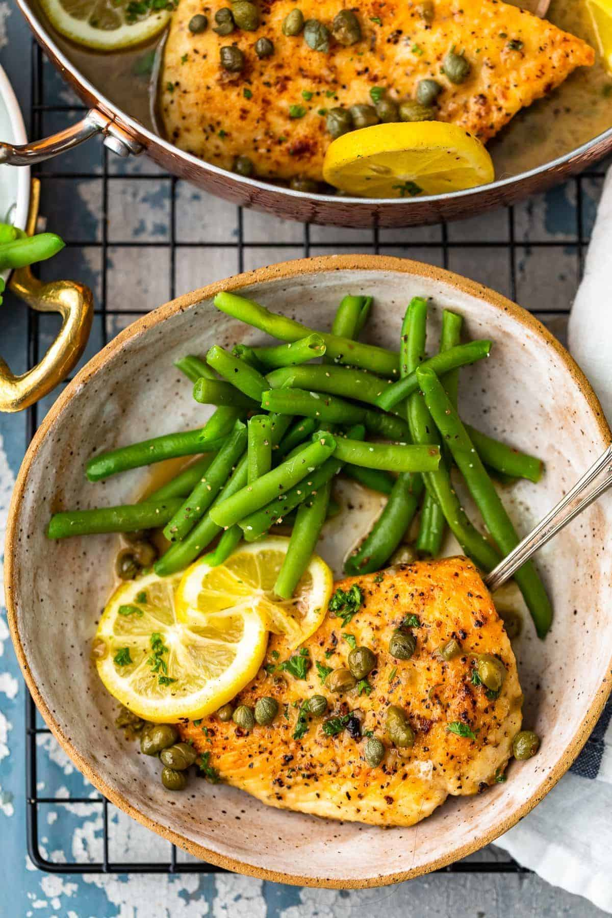 Chicken Piccata on a plate with green beans and lemon white wine sauce