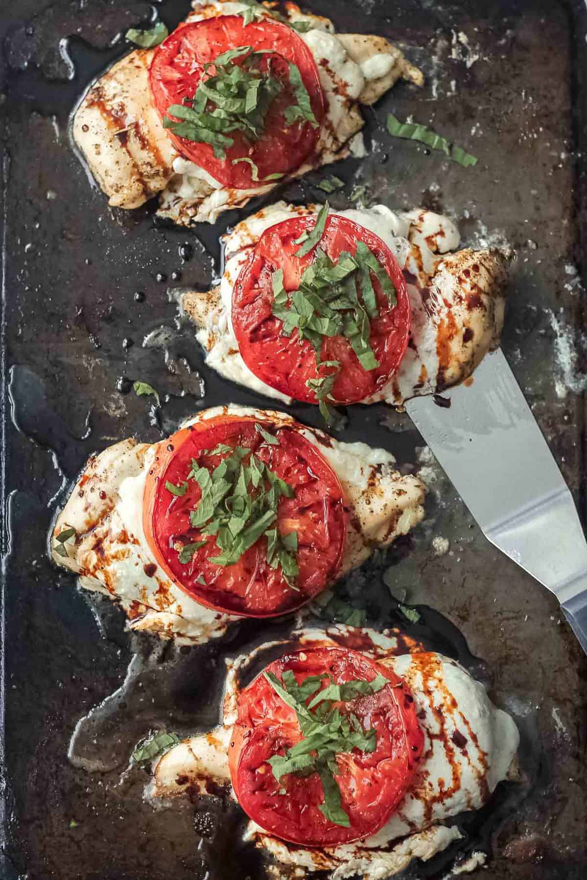 caprese chicken on a sheet pan with tomatoes cheese and basil