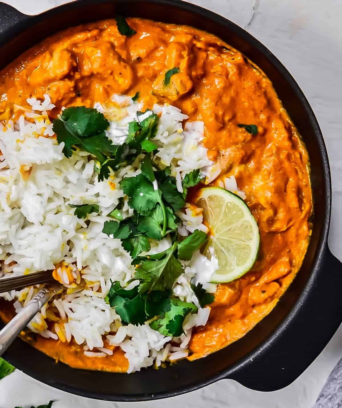 Overhead shot of Chicken tikka masala with rice and cilantro