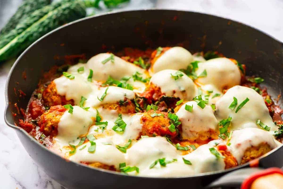 baked chicken meatballs with cheese in skillet