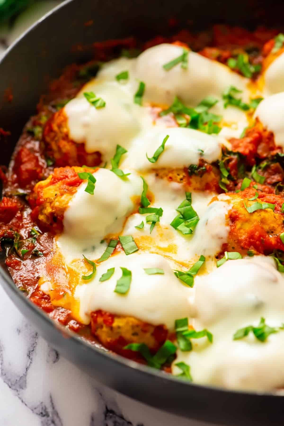 baked chicken meatballs in skillet covered with sauce and cheese