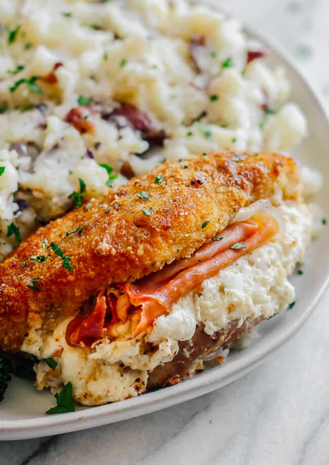 up close image of breaded chicken stuffed with prosciutto and cheese