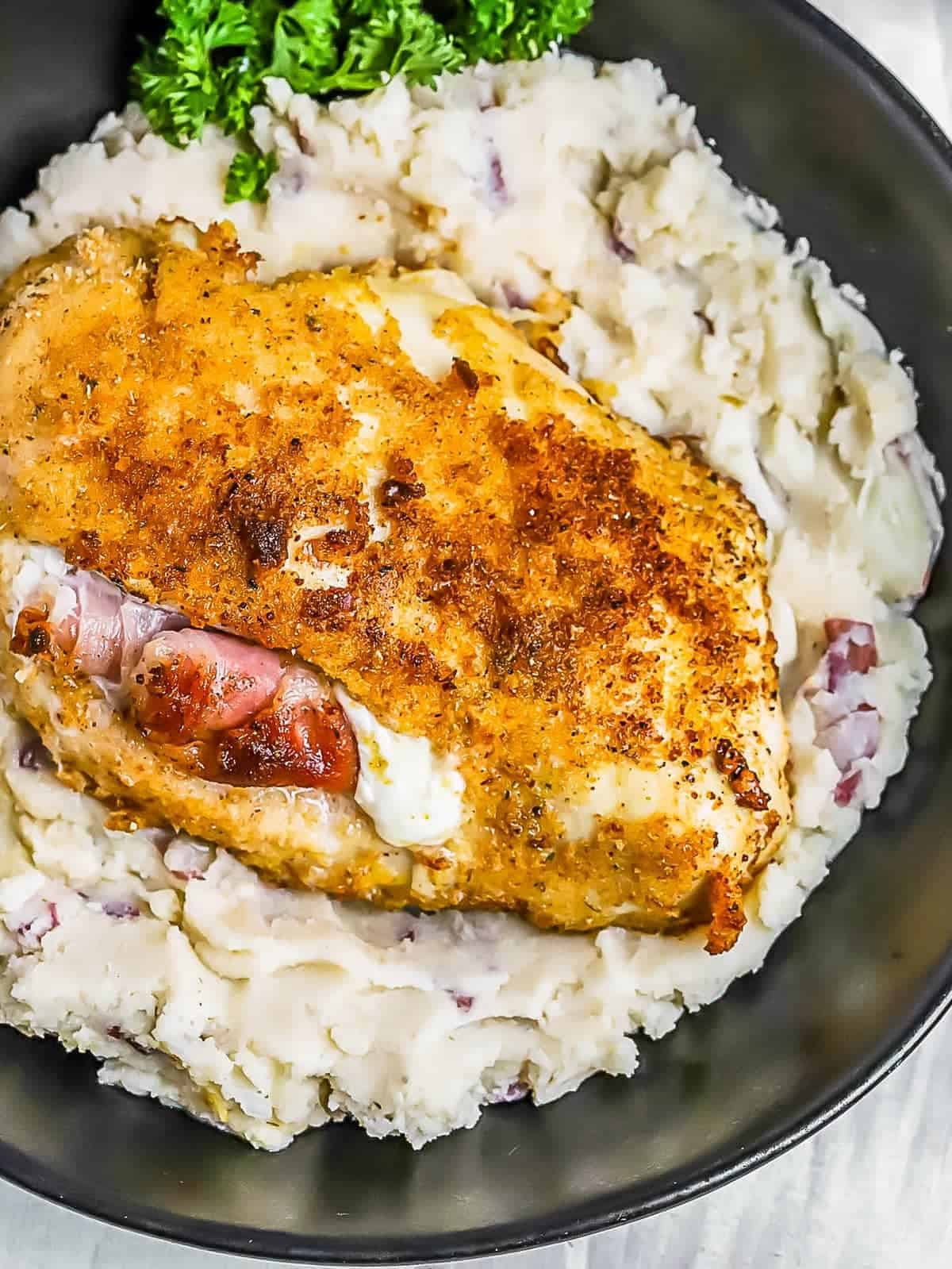 overhead shot of Prosciutto and Cheese Stuffed Chicken Breast over mashed potatoes in a bowl