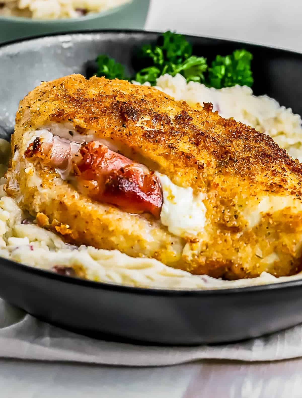 Prosciutto and Cheese Stuffed Chicken Breast over mashed potatoes in bowl