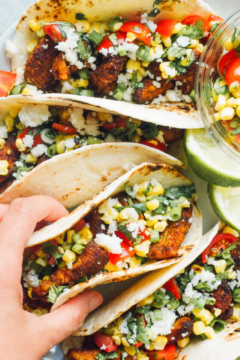 hand picking up cilantro lime chicken tacos