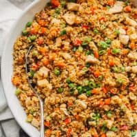 Quinoa Fried Rice is a healthy version of the take-out favorite and an easy one pan dish that's perfect for those busy weeknights. This Quinoa Fried Rice Recipe is chocked full of veggies and chicken; making it a wholesome, filling meal the whole family will love!