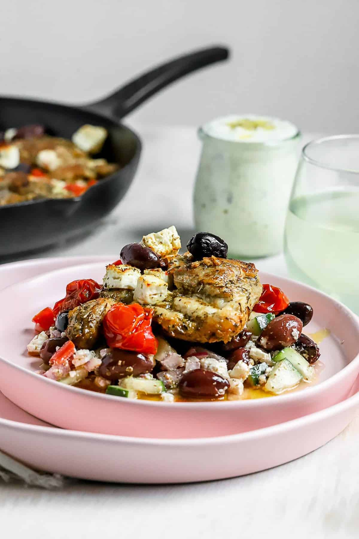 A greek chicken skillet meal served on a table