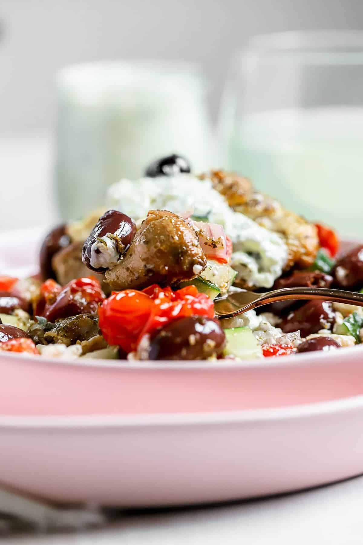 A greek chicken skillet meal in a light pink bowl