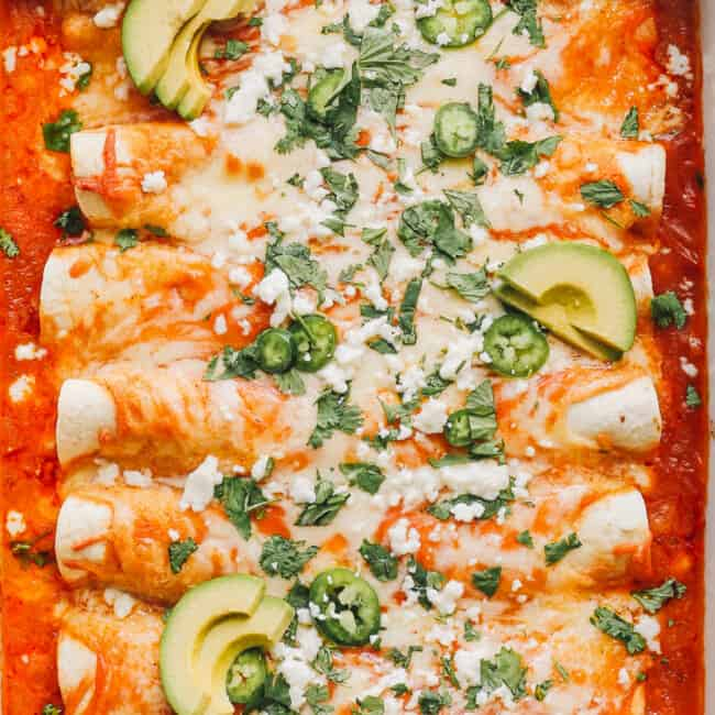 up close image of easy chicken enchiladas garnished with sour cream and cilantro