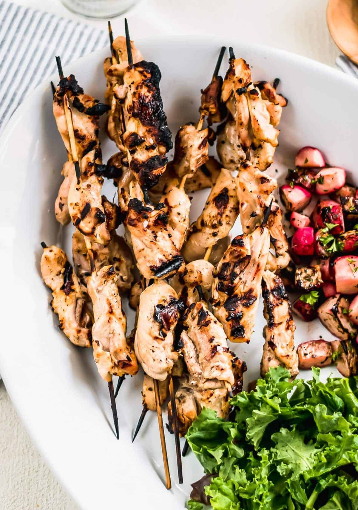 Grilled chicken kebabs on a large white serving plate