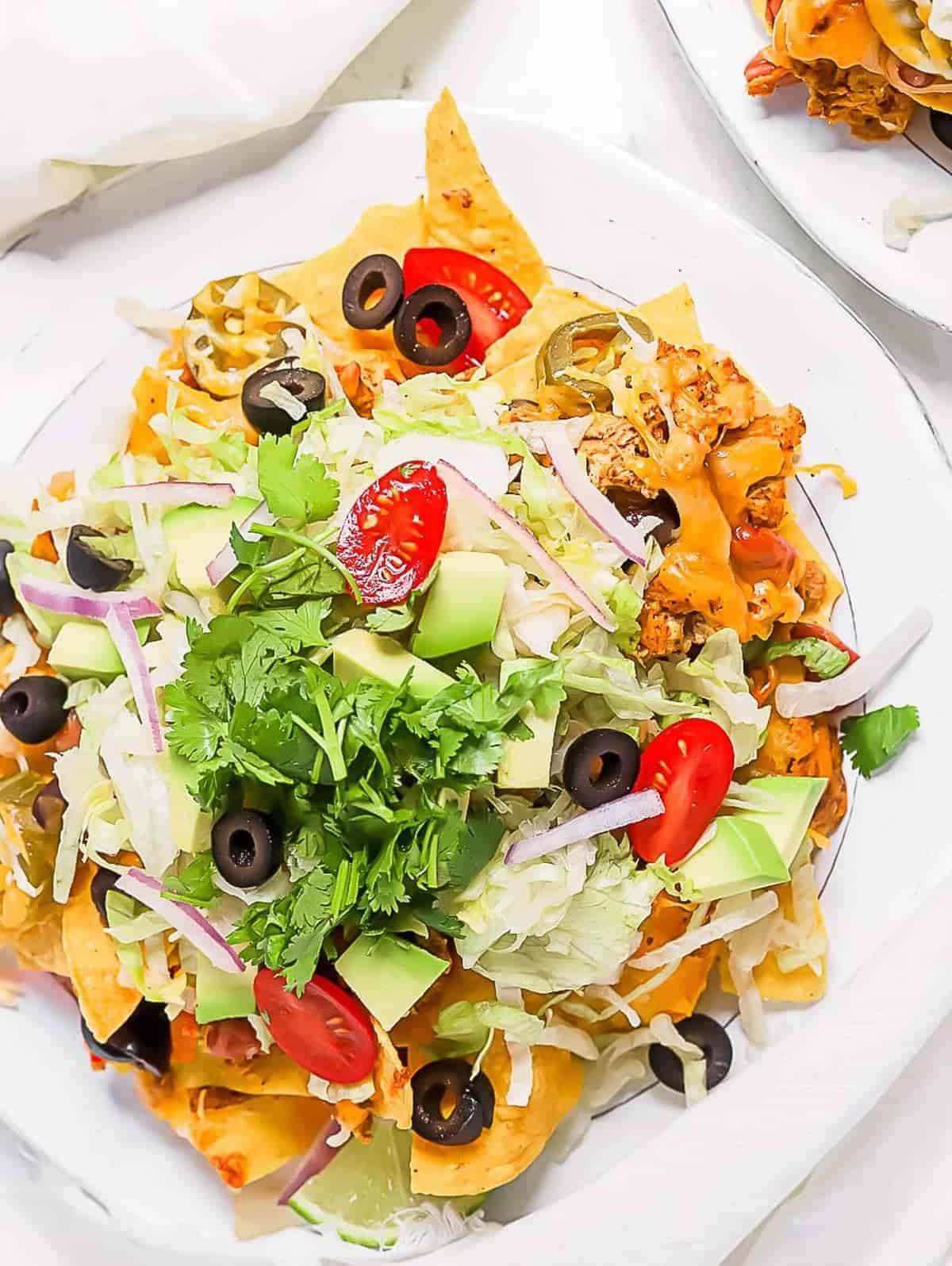Top down shot of chicken sheet pan nachos on a white plate