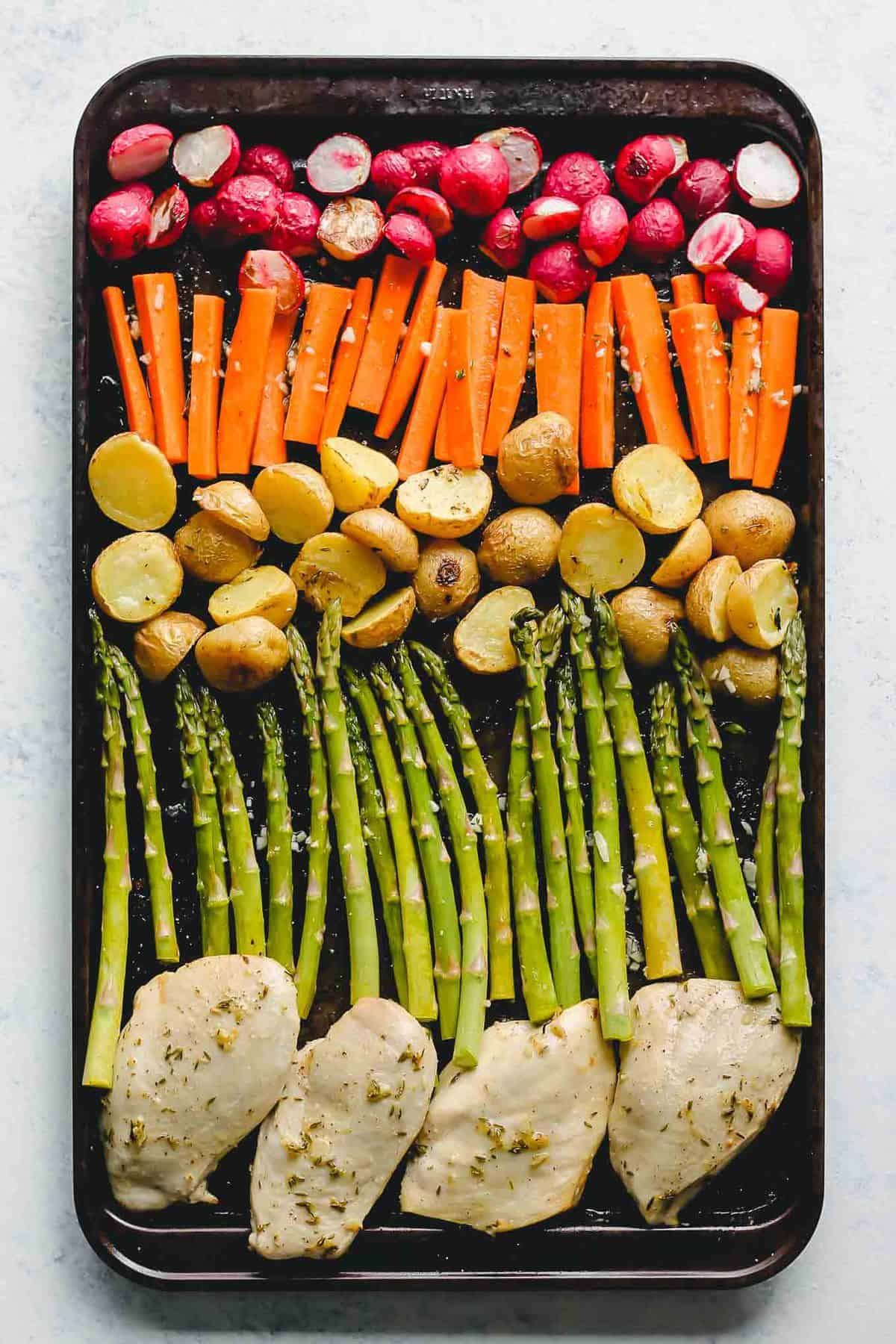 uncooked herb chicken and vegetables on a sheet pan