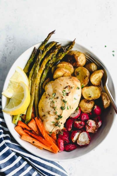 Cooked herb chicken in a bowl with roasted vegetables