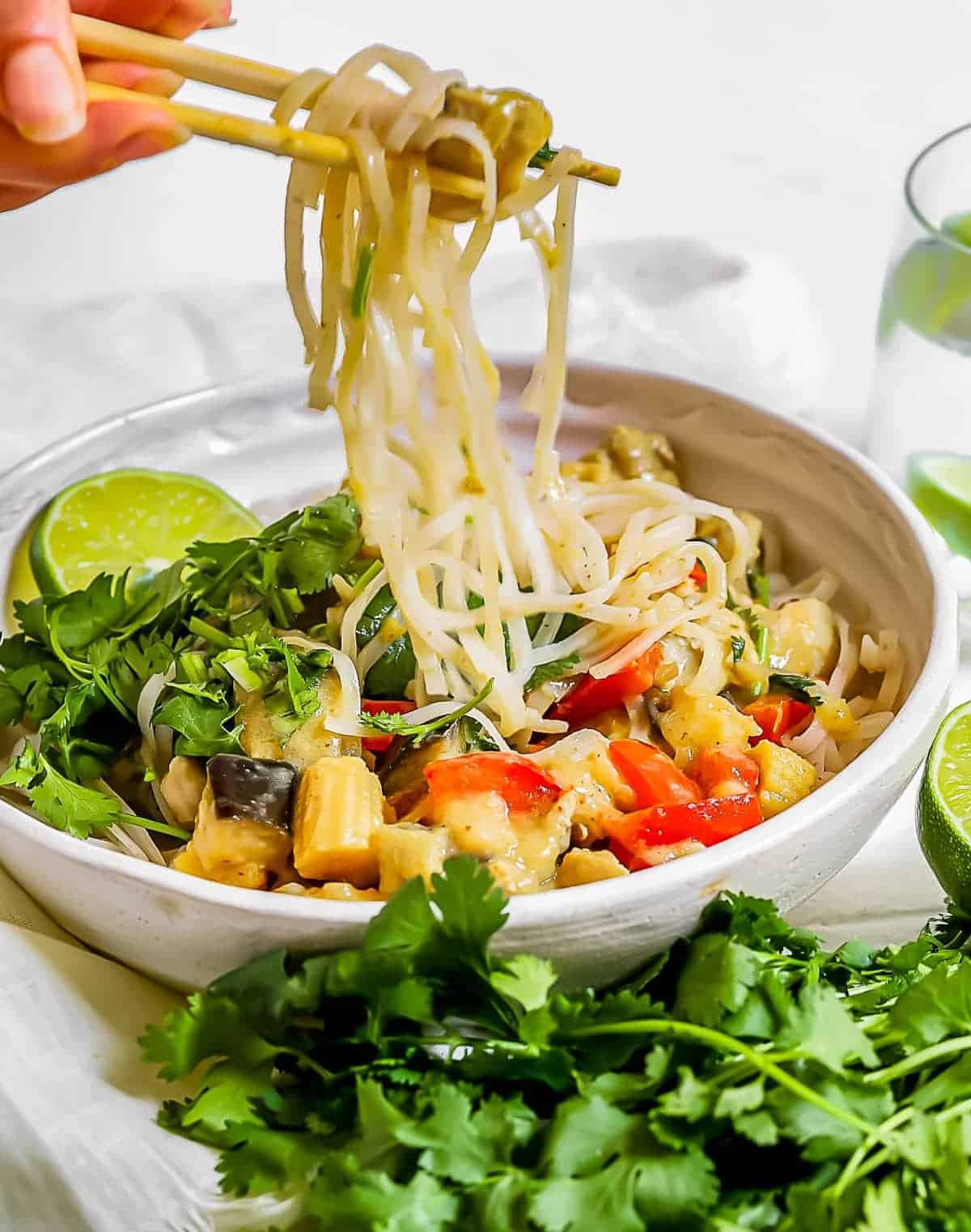 Chopsticks picking up noodles form the thai curry chicken bowl