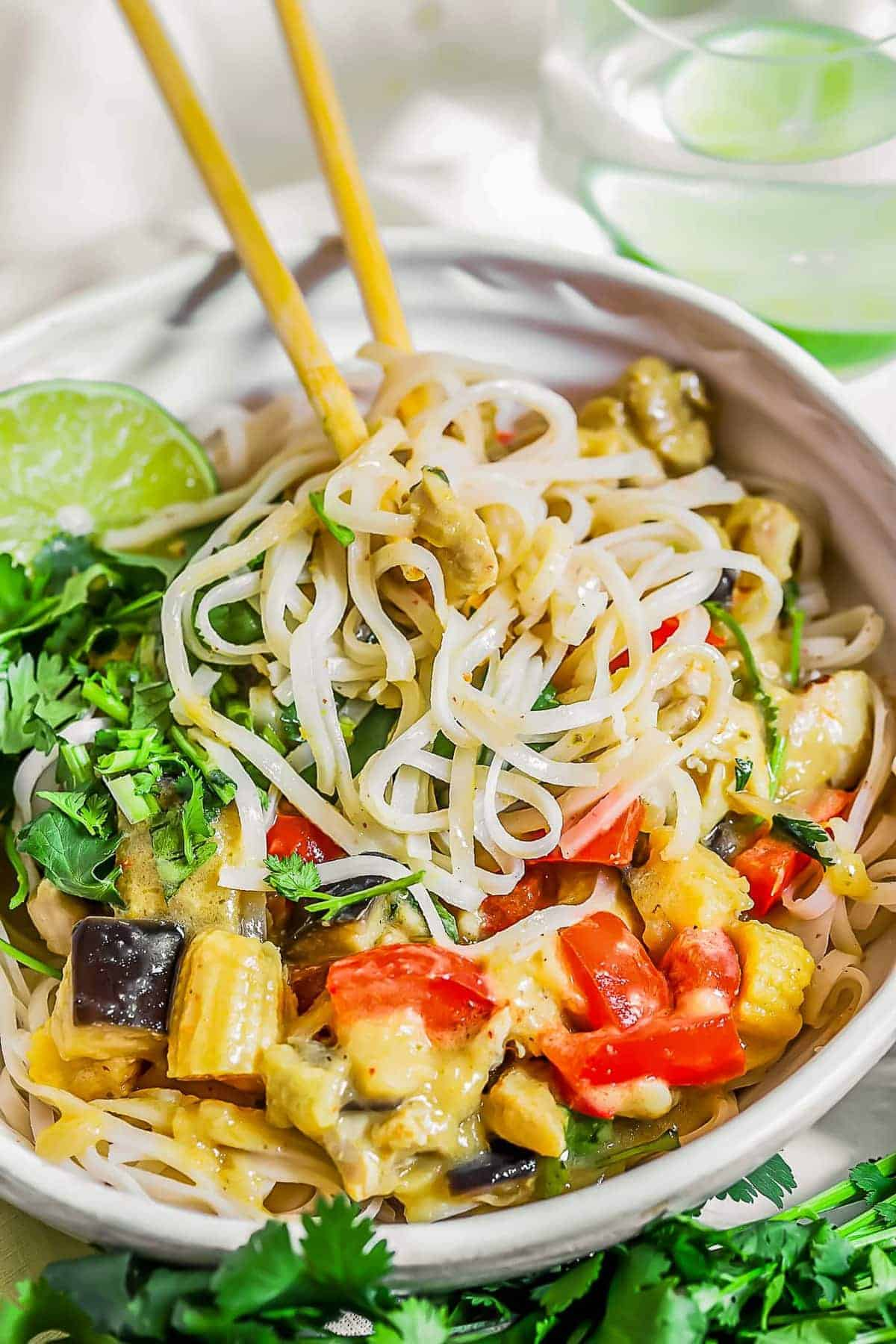 Close up of chopsticks in a Thai green curry chicken noodle bowl