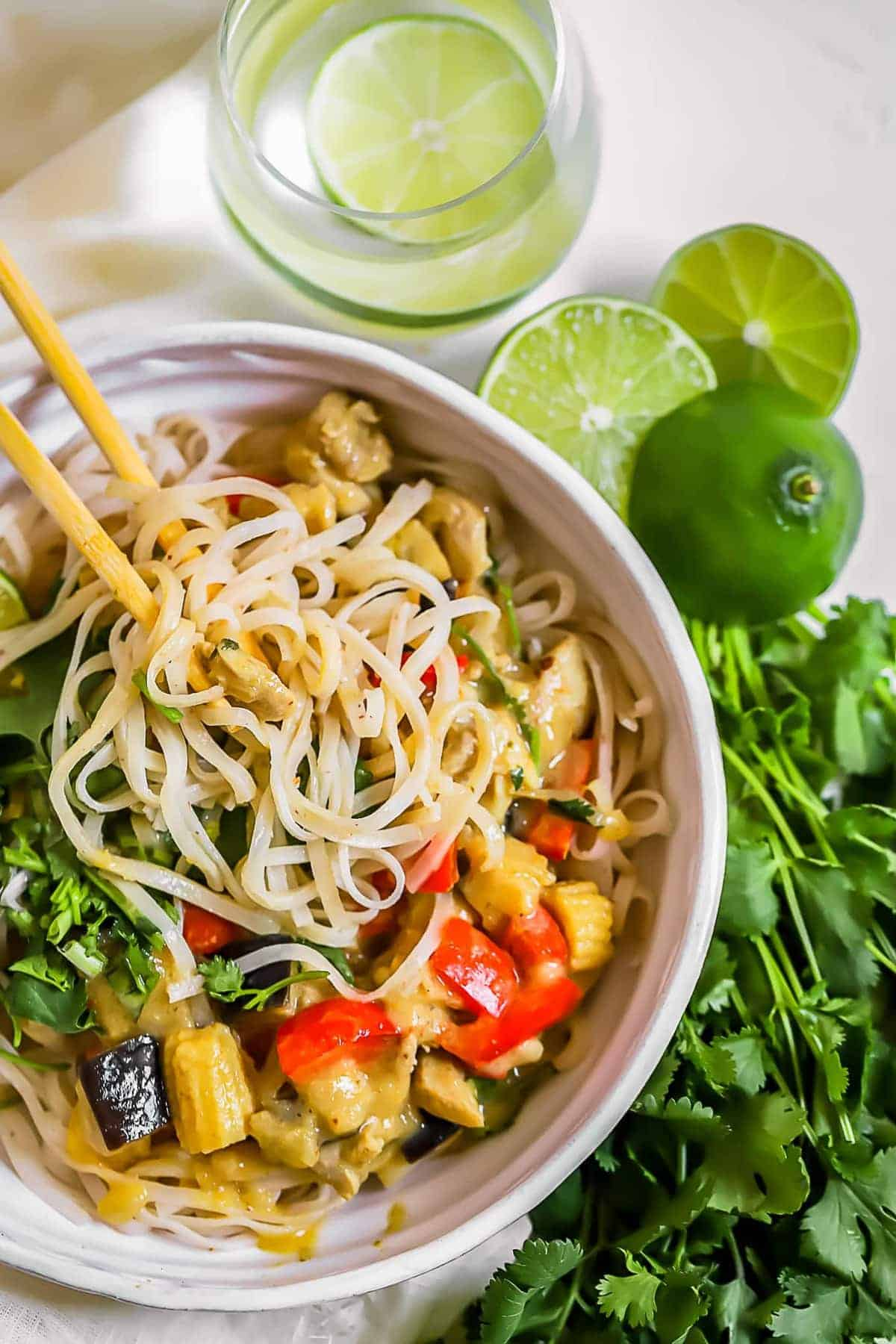 Top shot of a Thai green curry chicken bowl with chopsticks