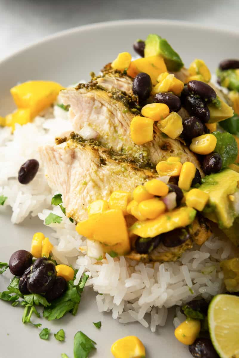 sliced cilantro lime chicken breast topped with mango avocado salsa