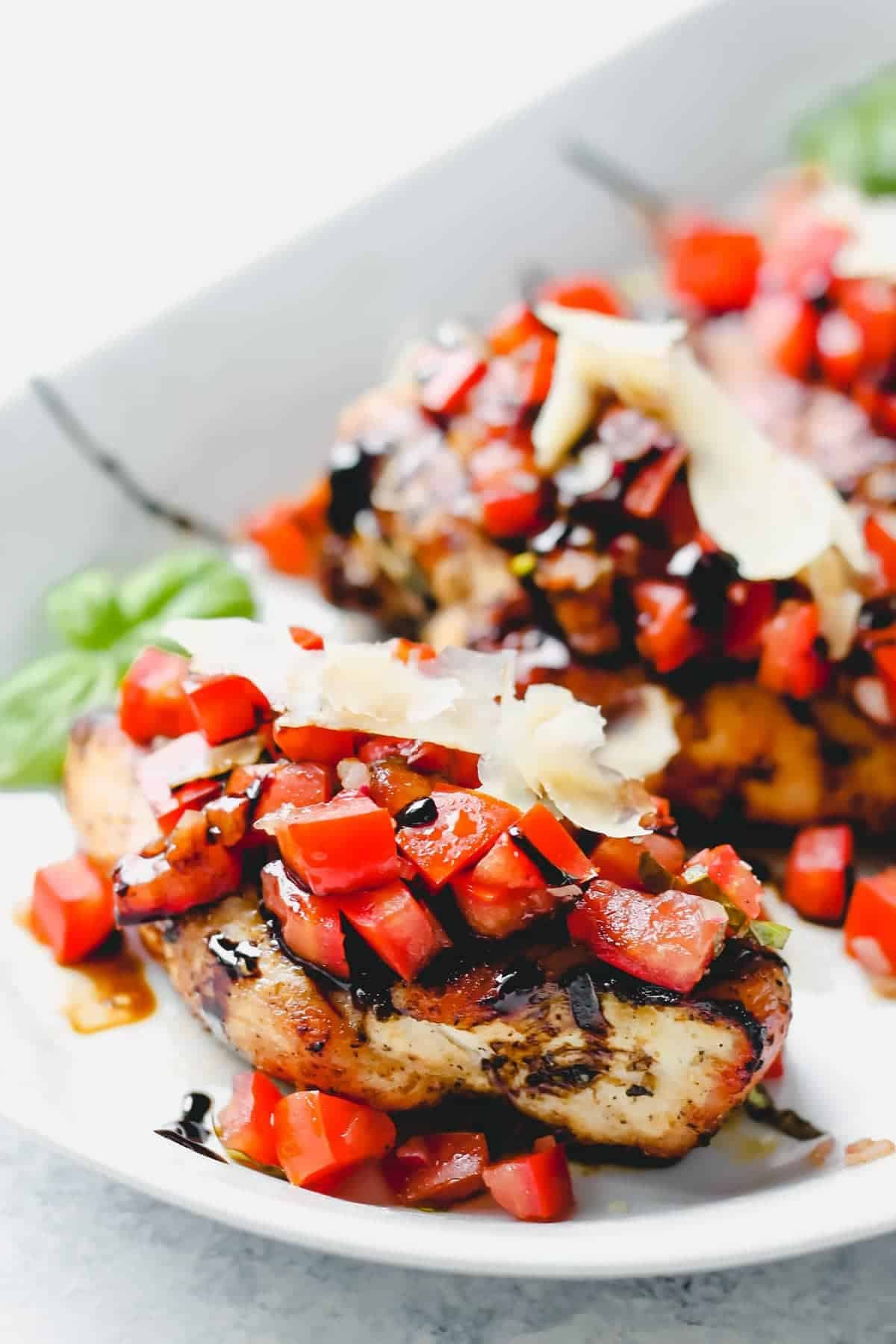 Close up of chicken topped with tomatoes and parmesan