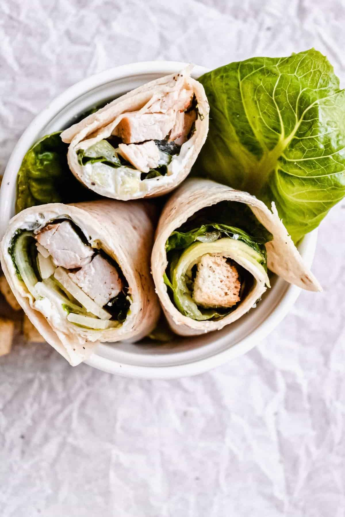 Three chicken caesar salad wraps served in a small bowl