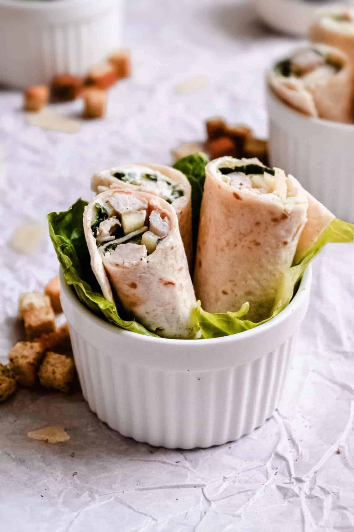 Chicken Caesar Salad wraps served with a lettuce leaf in a ramekin