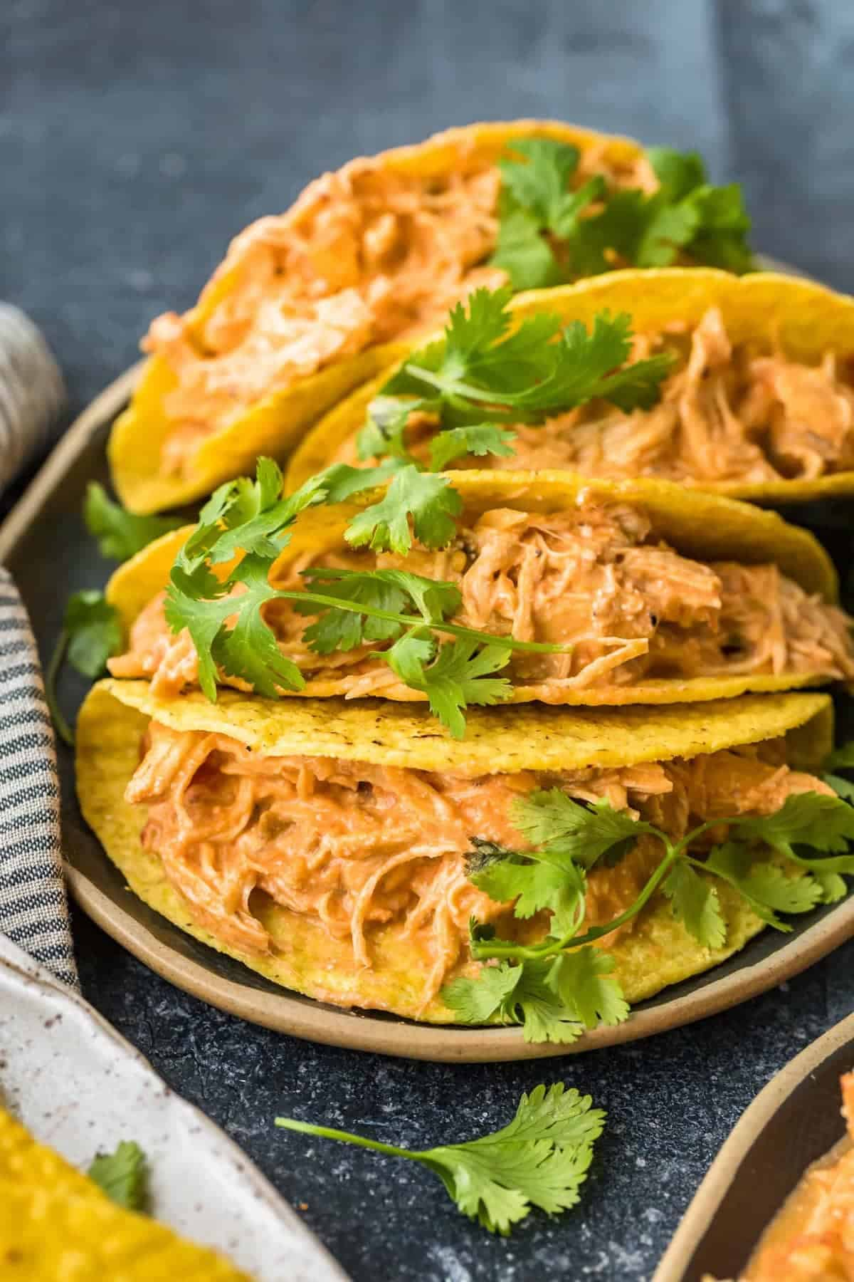 Four chicken tacos on a serving plate