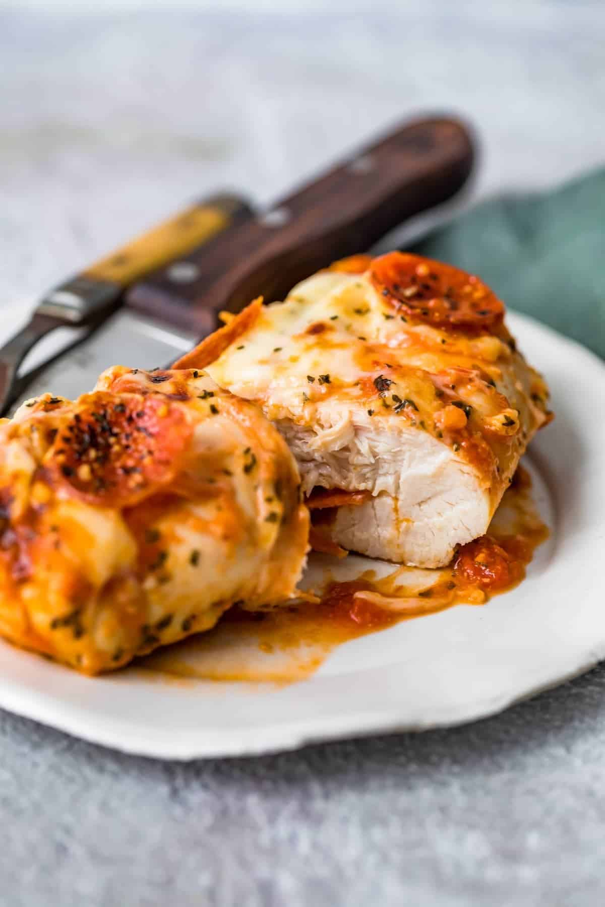 A Pizza Chicken Baked breast served on a white plate and cut in half