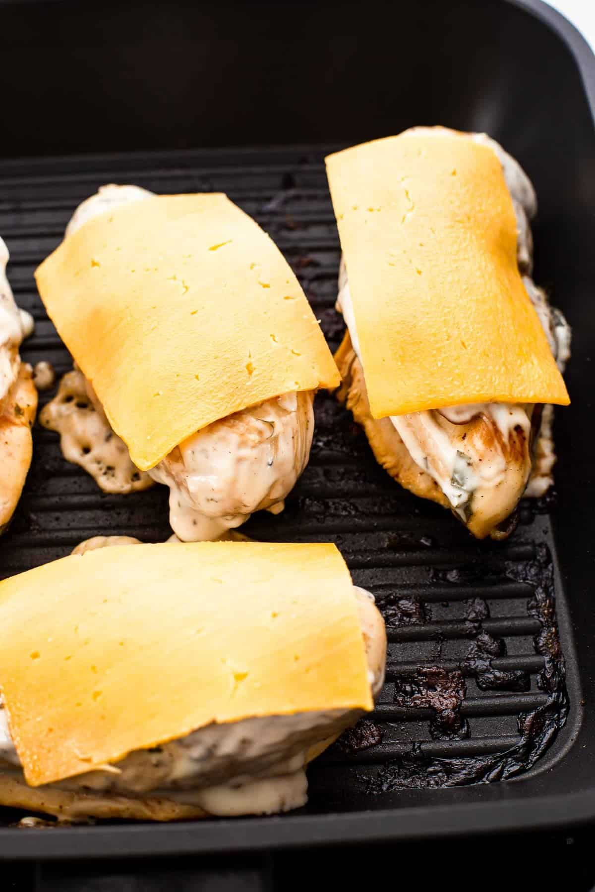Cheese slices on chicken breasts in a pan