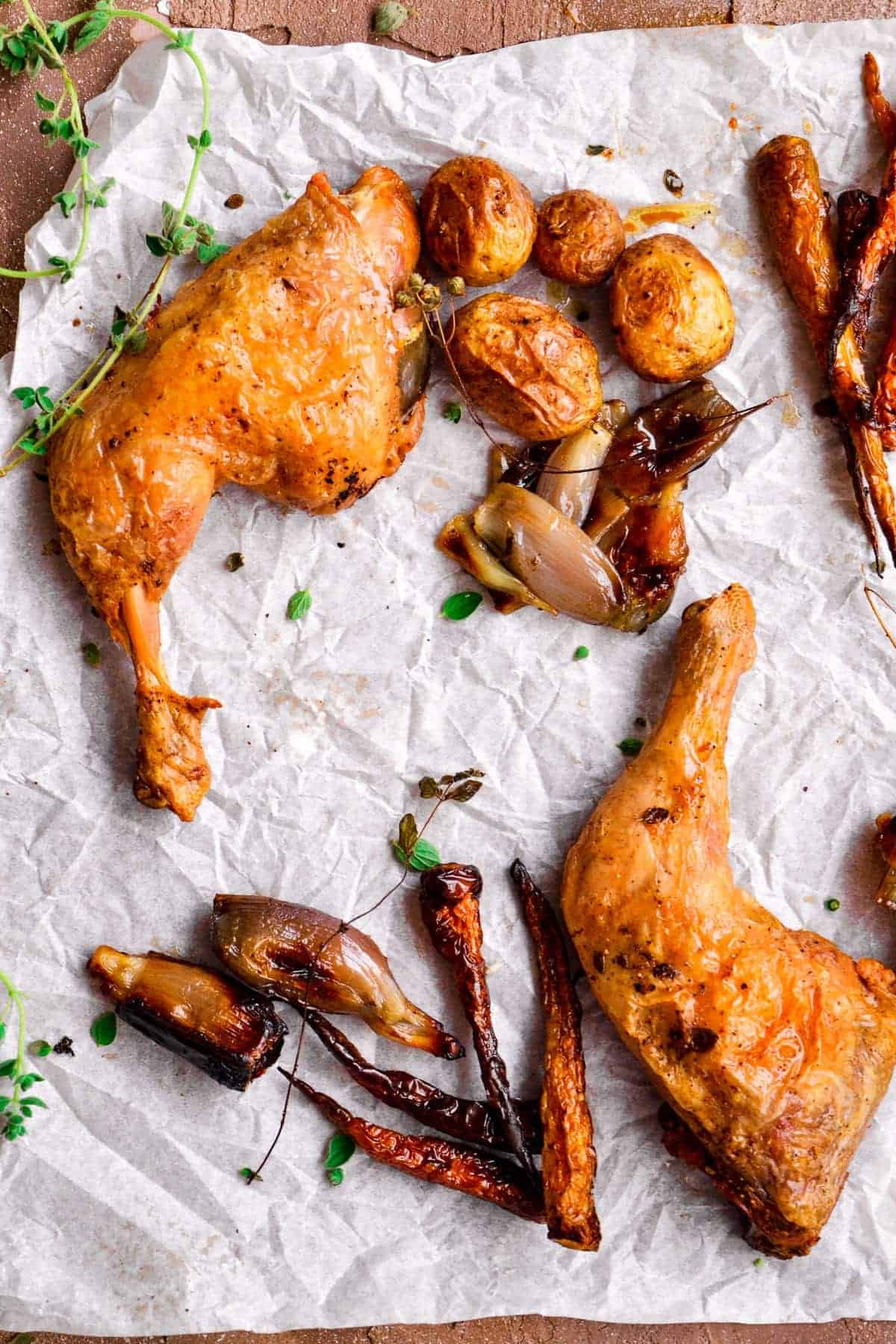 Baked Chicken and Potatoes on parchment paper with carrots and fresh herbs