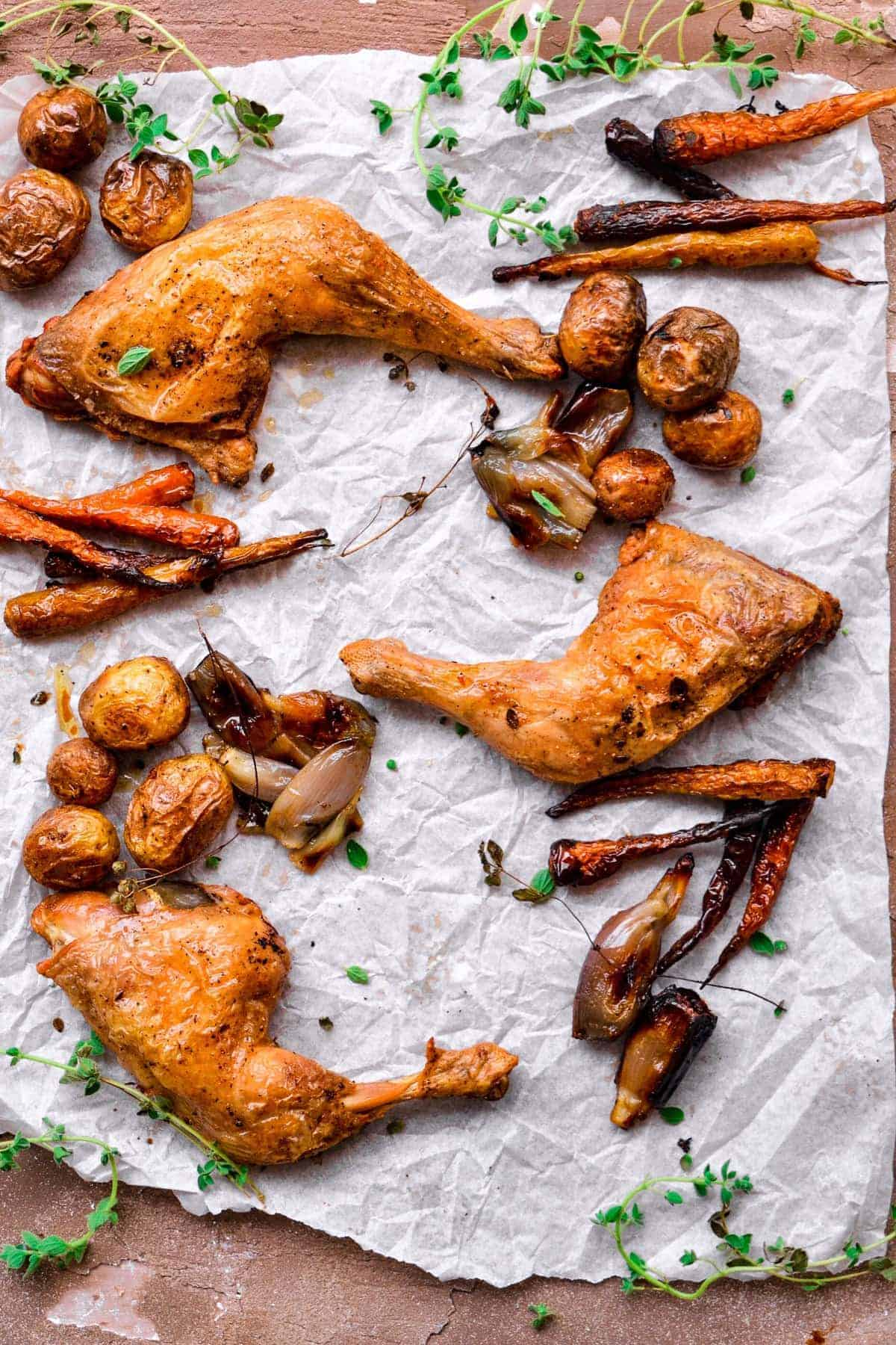 Baked Chicken and Potatoes sheet pan meal on parchment paper with fresh herbs
