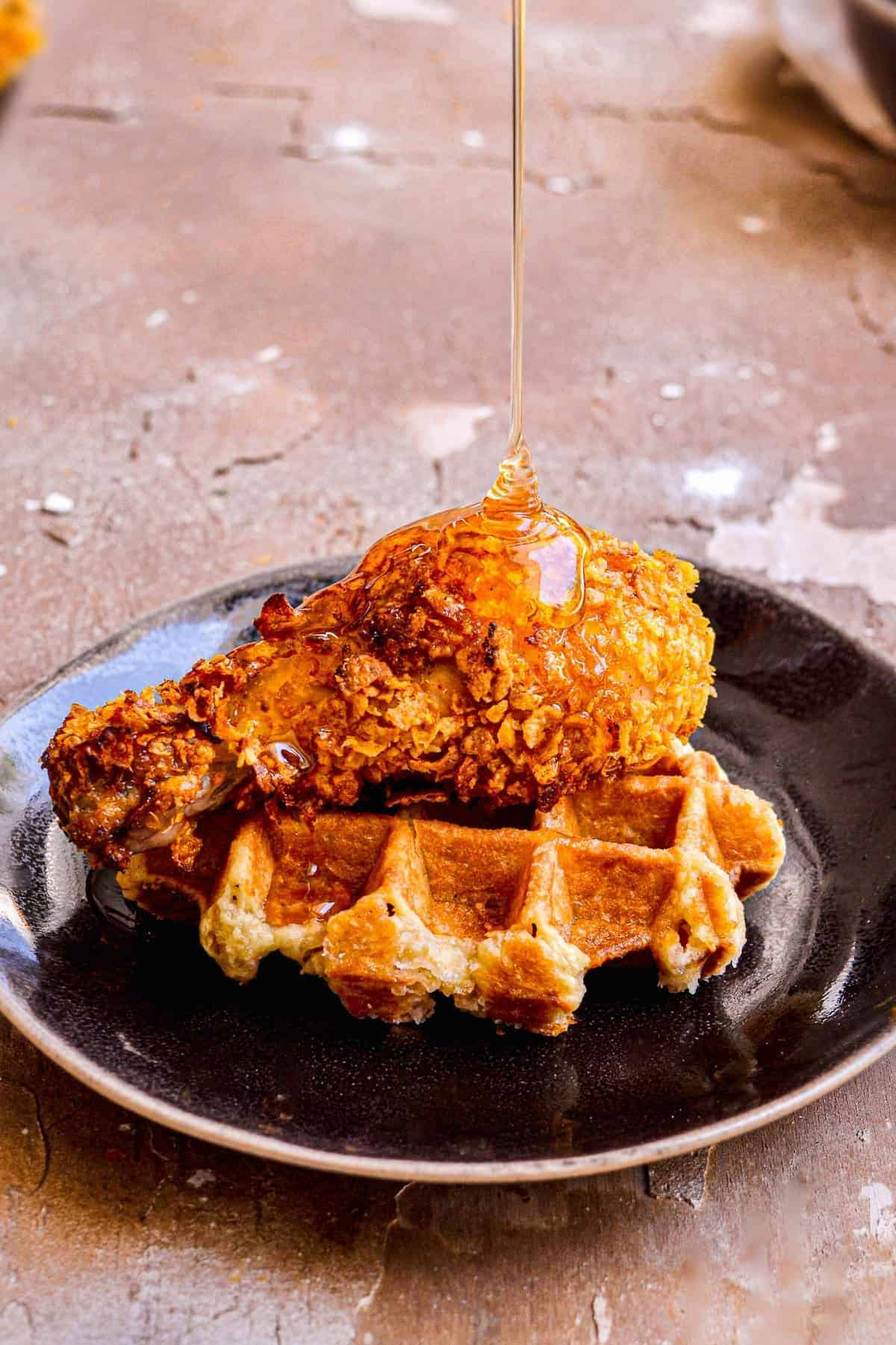 Honey being drizzled on Chicken and Waffles