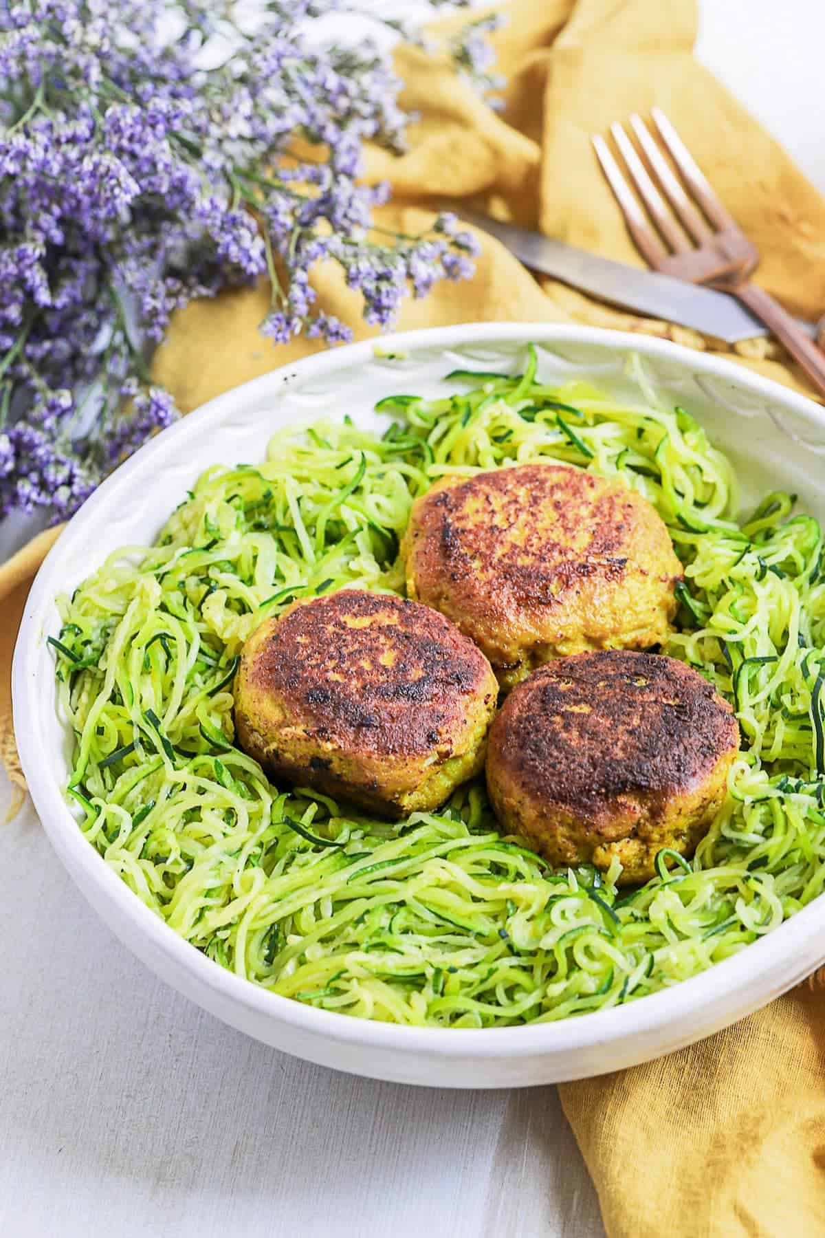 Meatballs served with zoodles in a white bowl