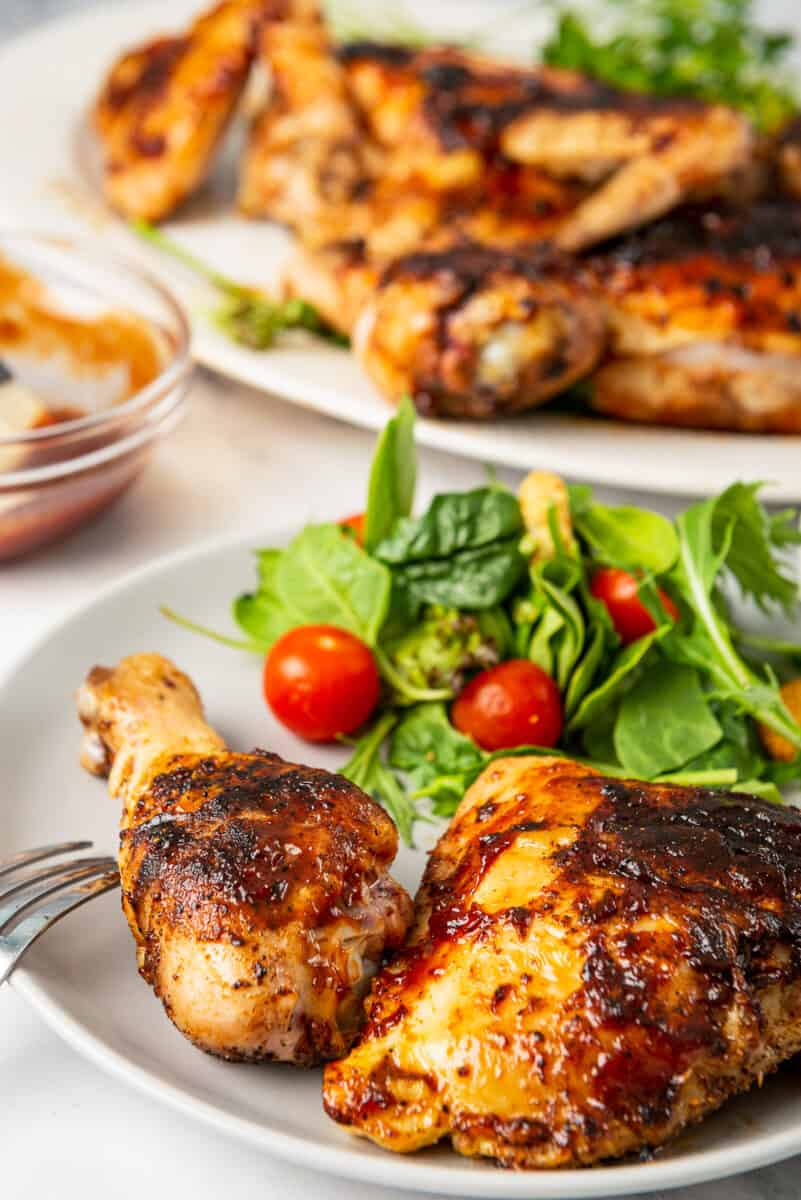 bbq chicken drumstick and thigh on plate with salad