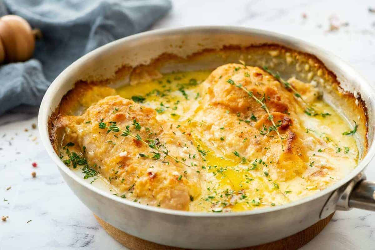 Butter baked chicken in a white oven pan