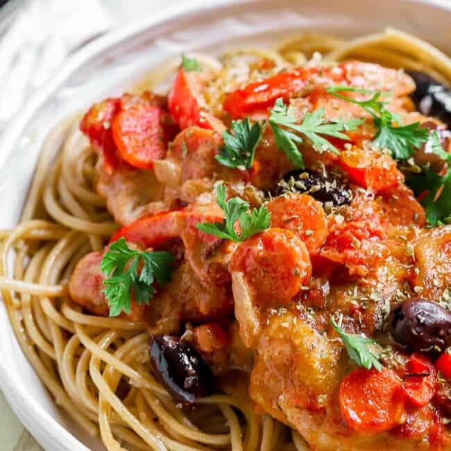 chicken cacciatore over pasta on plate