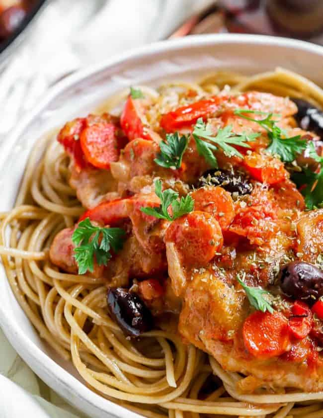 chicken cacciatore over pasta on plate