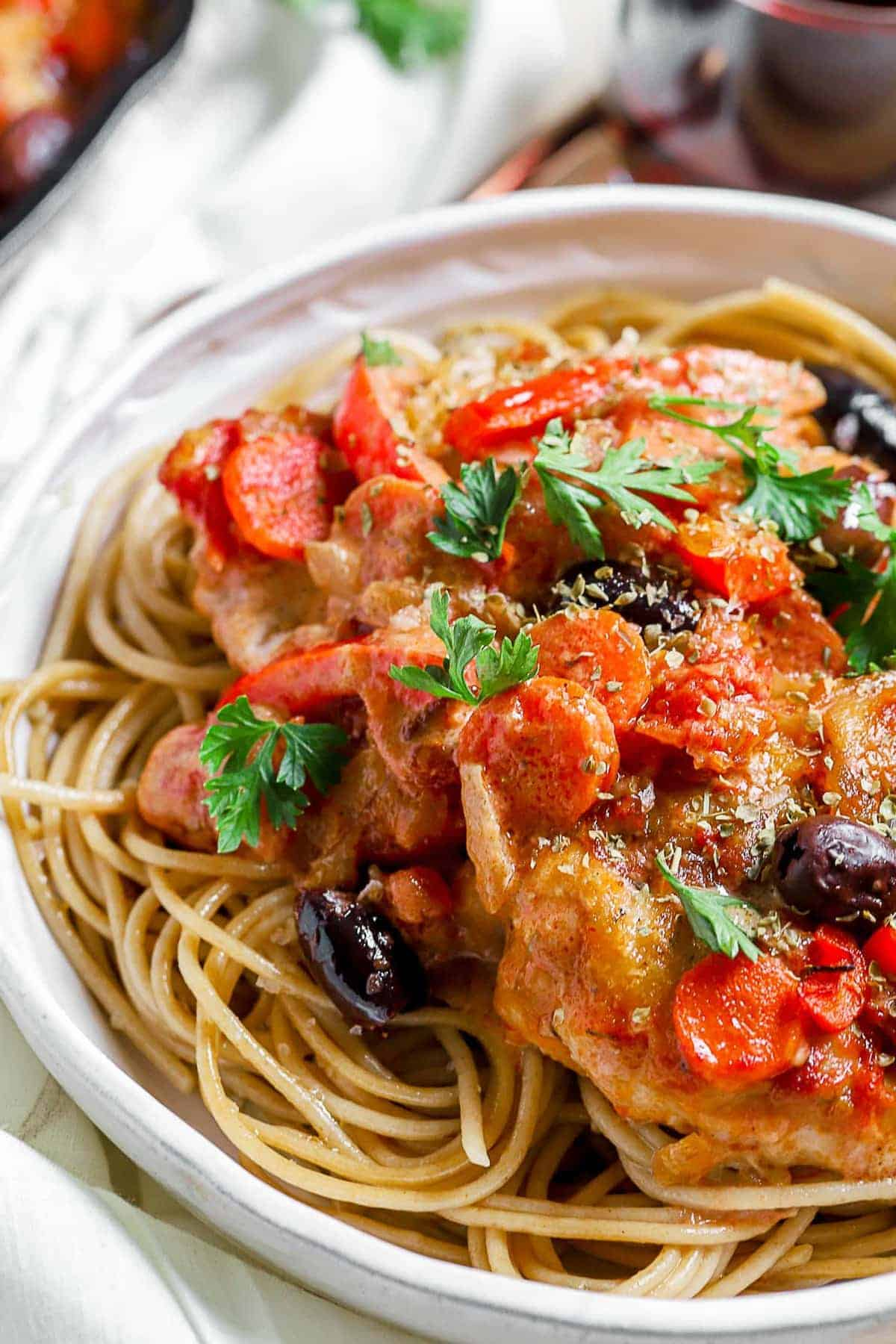 Chicken Cacciatore served with pasta in a white bowl