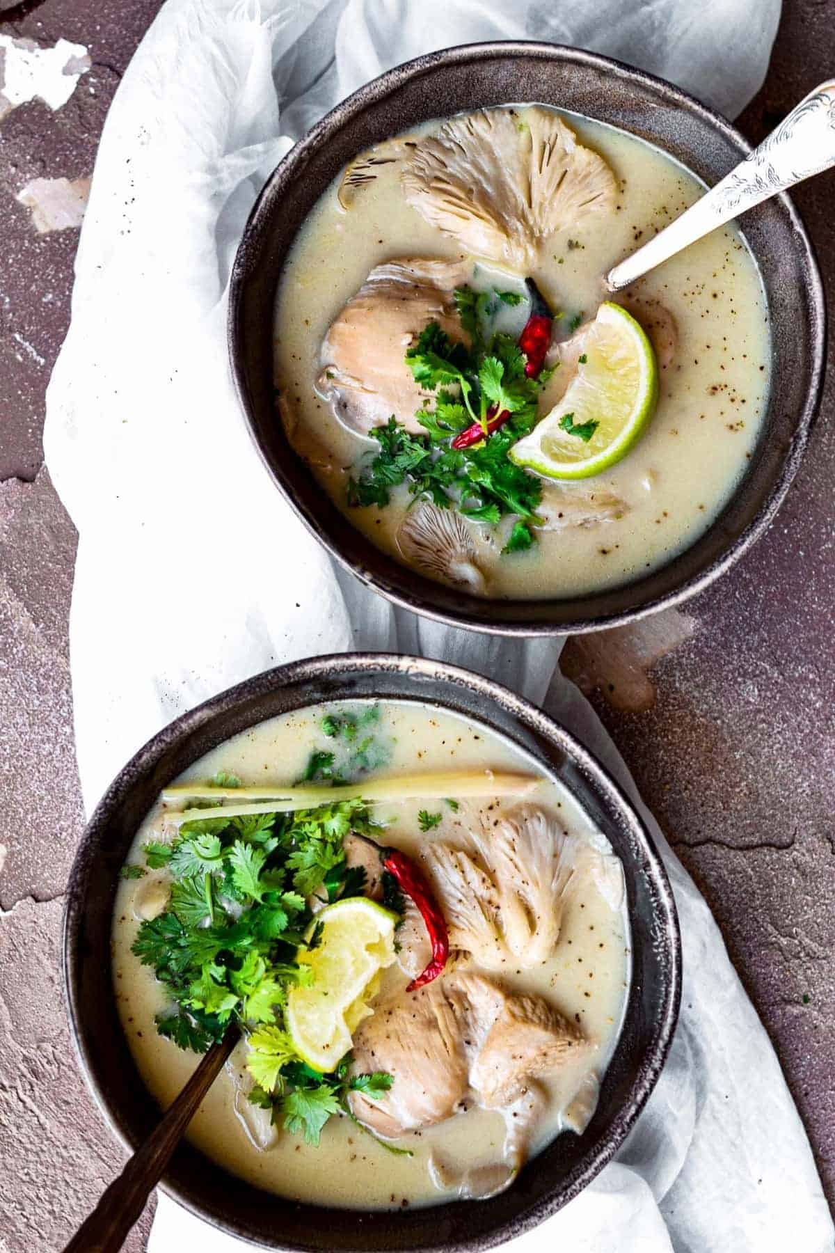 Chicken Coconut Soup topped with lime wedge and fresh herbs