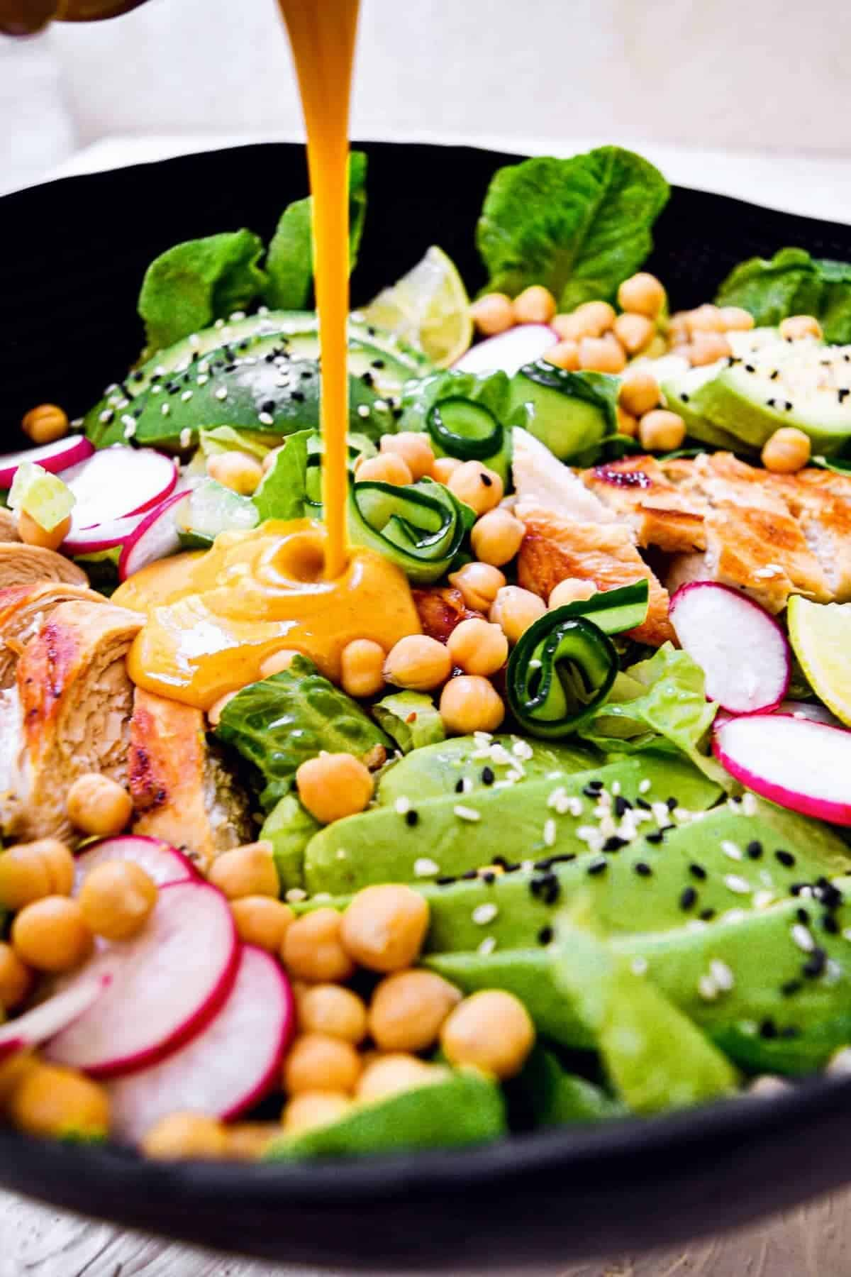 honey and mustard dressing being poured over salad