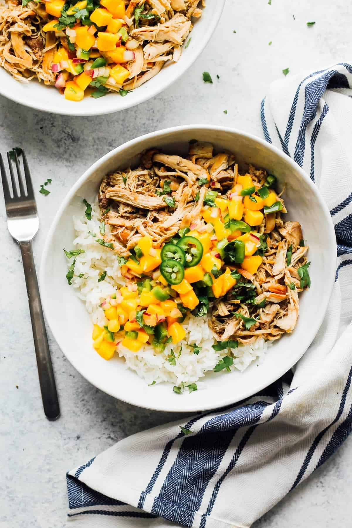 Instant pot jerk chicken served with rice and fresh mango in a bowl