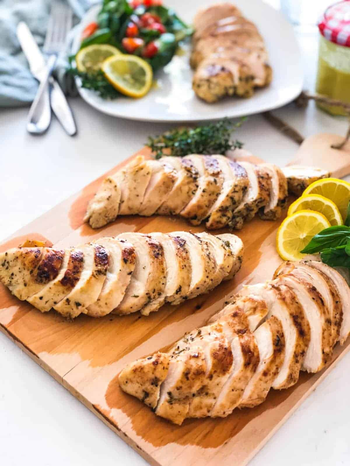 Three sous vide chicken breast sliced on a chopping board