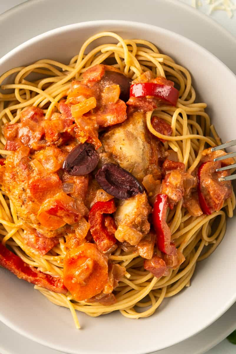 up close image of chicken with sauce, olives, and pasta