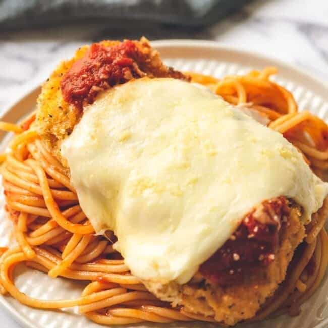 chicken parmesan on a plate over pasta