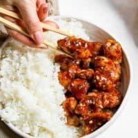 chopsticks holding a piece of chicken