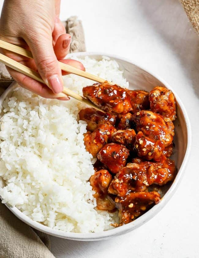 chopsticks holding a piece of chicken