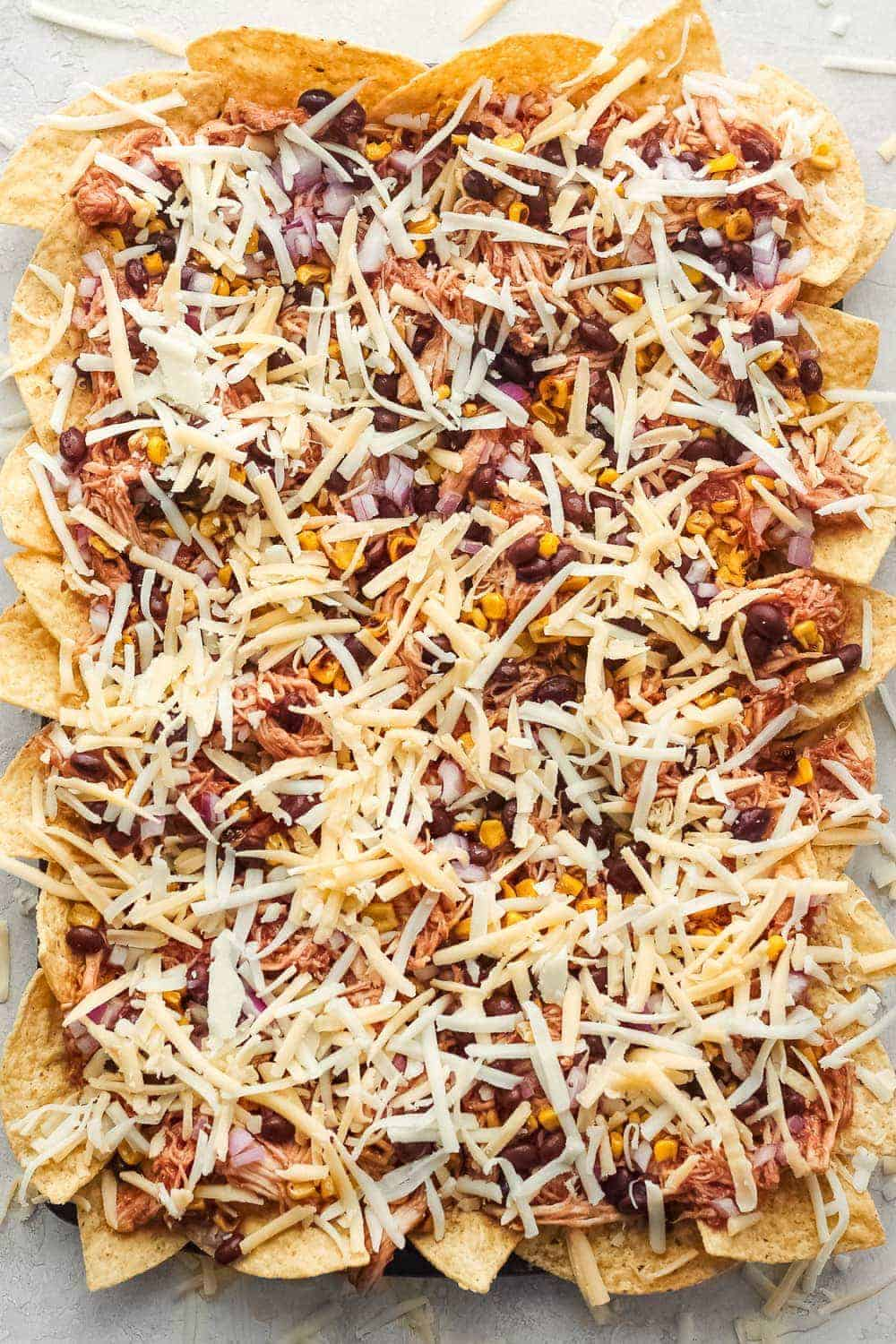 The nachos on a sheet pan before being cooked