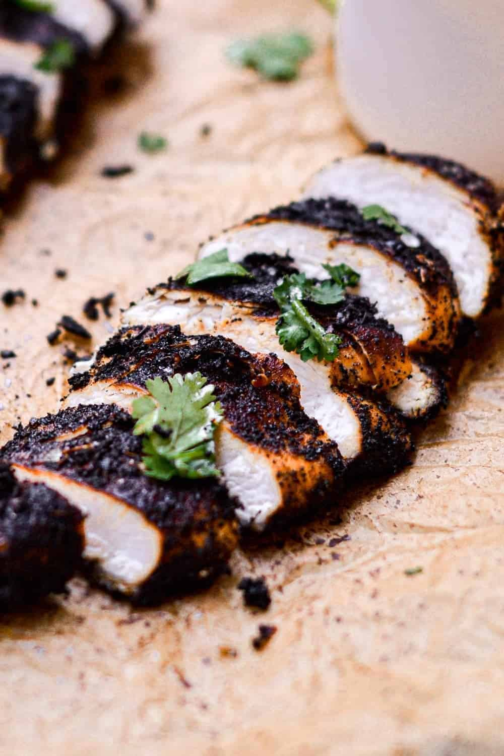 Blackened chicken garnished with fresh herbs