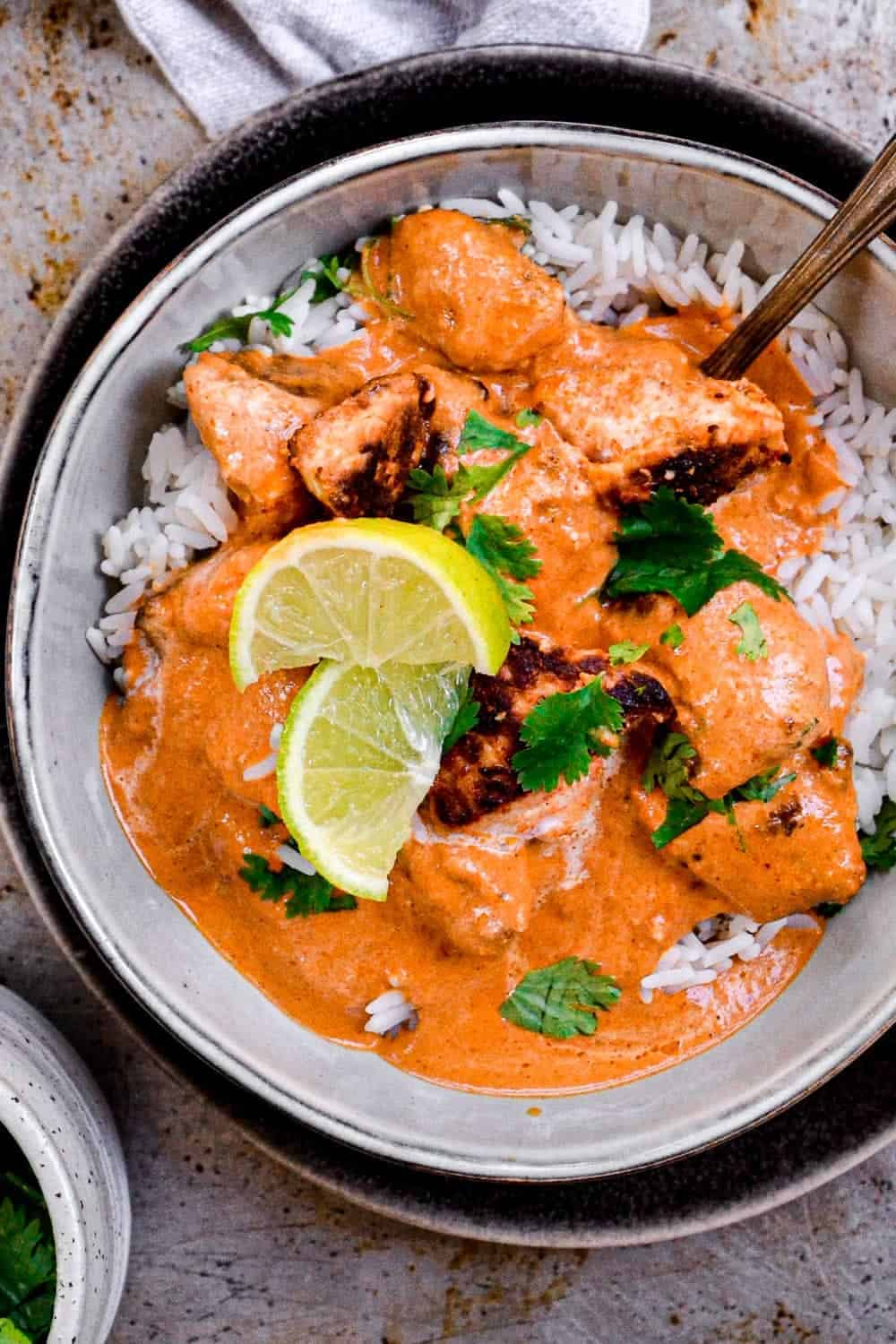 Butter chicken served in a bowl with rice and lime wedges