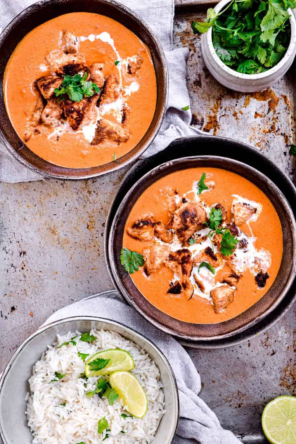 Two bowls of butter chicken ready to eat